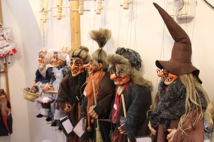 Puppets hang grinning inside a souvenir shop in Prague