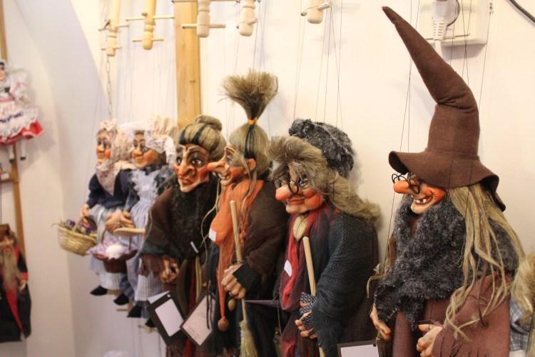 Puppets hang grinning inside a souvenir shop in Prague