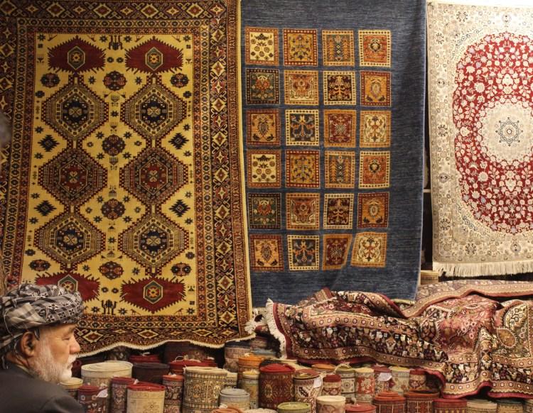 An old Irani trader displays Persian carpets at a souk in Sharjah.