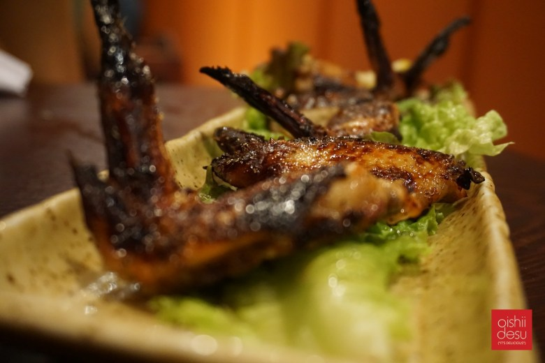 Photo Description: teba or chicken wings are on a very long rectangular plate with a lettuce beneath for plating purposes and 4-5 wings with a very nice char.