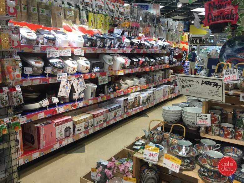 Photo Description: the interior shot of Tokyo Central is FILLED with products from floor to ceilings. In this shot you can see a row with multiple shelves of rice cookers, along with maki su, and dinnerware.