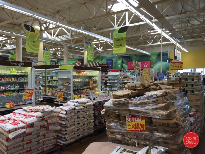 Photo Description: the newly designed and built Seiwa market that took over the old Fresh and Easy. The green and muted yellow color palette is in the background with several pallets of rice in the foreground.