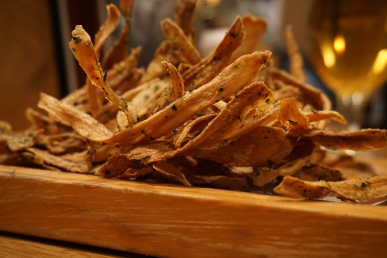 Photo Description: on top of a large slab of wood sits a bunch of fried burdock root. They are long golden strips with specks of aonori (seaweed flakes).