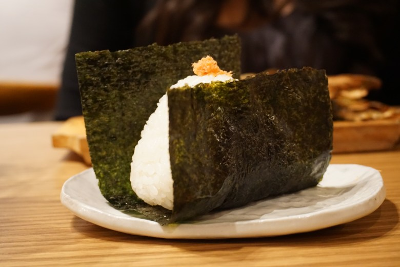 Photo Description: a single small white plate that looks rustic. On top of the plate is onigiri (rice ball) wrapped in a piece of nori (seaweed).