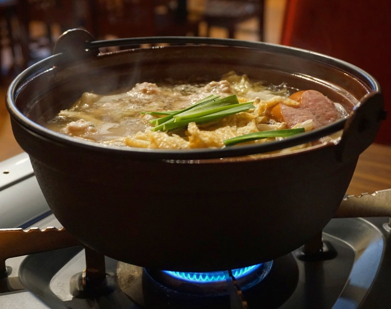Photo Description: this is what chanko nabe looks like which is a cast iron pot with a stew looking food in it. Inside the pot is a number of ingredients from cabbage to meat and number of other ingredients.