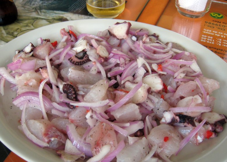 Photo Description: Best Ceviche Ever image is from Lima, Peru. Chunks of octopus are cute up with sliced red onions sprawled out the plate with what looks like pepper and little red bits that I can not identify.