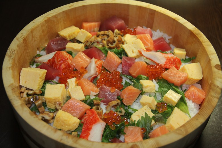Photo Description: Chirashi-zushi in a Japanese hangiri has sushi rice, along with oba shiso, large chunks of tuna, tamago, ikura, to fake crab (kani).