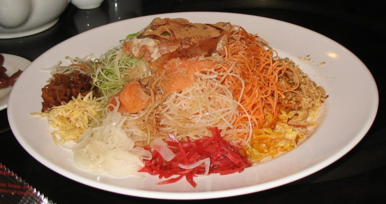 Photo Description: Singapore Yusheng which is several ingredients on one round white plate. Each ingredient is julienned from what looks like carrots, beni shoga?, to green onions, and a number of other ingredients.