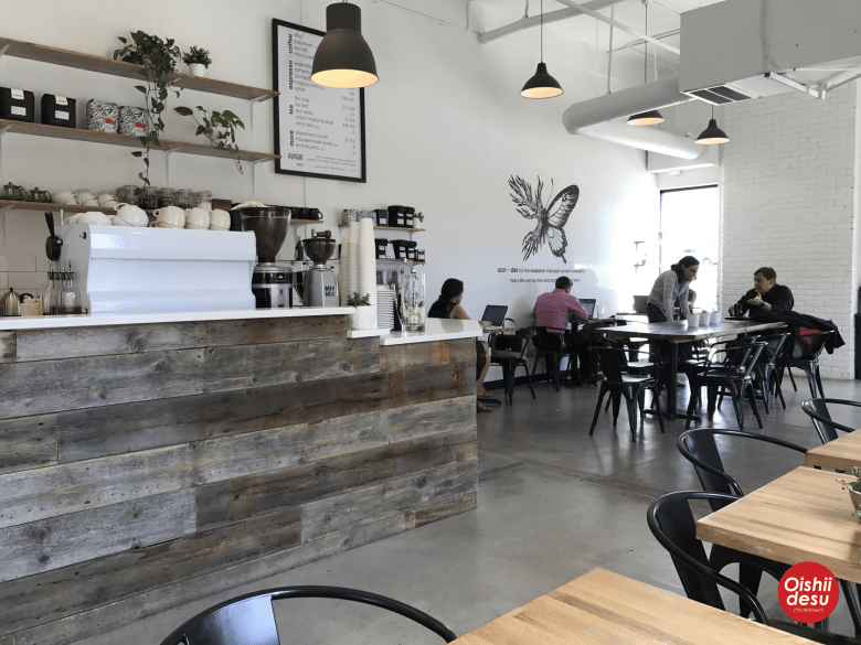 Photo Description: Sonder Coffee and Tea, in Southeast Denver. The open ceiling and interior is a very start white with black accents. The main bar looks like reclaimed wood, with black chairs and an illustration of a butterfly of some sorts on one wall.