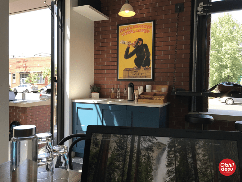 "Photo Description: Blue Sparrow Coffee in River North aka the dumbass gentrification label of ""Arts District."" Inside, a brick exposed wall, with a Carlo Biscaretti ""drunken monkey"" poster."