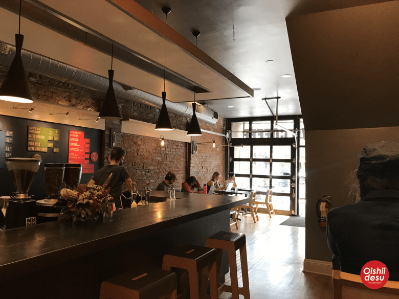 Photo Description: Novo Coffee house in West Highland. Another place with garage style roll up door. The interior is fairly small with only four 2-tops lining the front entrance, along with bar seating allows up to 4 additional people.