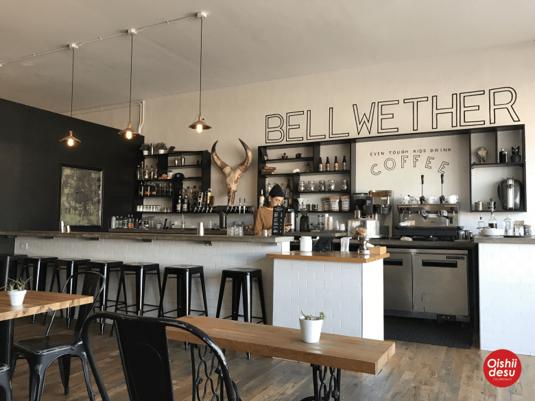 "Photo Description: The Bellwether in South Park Hill. ONe dude is standing behind the bar area with the giant typography painted on the white wall ofthe black and white motif that says ""BELLWETHER and Even Tough Kids Drink COFFEE."""