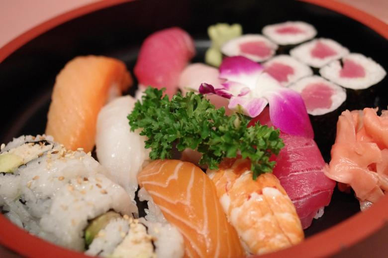 Photo Description: Matsu sushi in Huntington Beach is of a large traditional round plate with a black laquer inner, with a outer red color. In the plate there is a makizushi roll, a hosomaki, and nigir sushi ranging from tuna, tuna, iak, shrimp, and tuna. In the corner is a mound of pink sliced ginger, wasabi, and a sprig of parsley and a Hawaiian style flower.