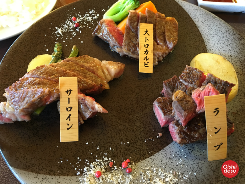 Photo Description: Steak and beef cuts all demarcated on the plate, so that you know which cuts of wagyu you are about to eat. There are three cuts on the plate all of which are being accompanied by vegetables and what looks like potatoes.
