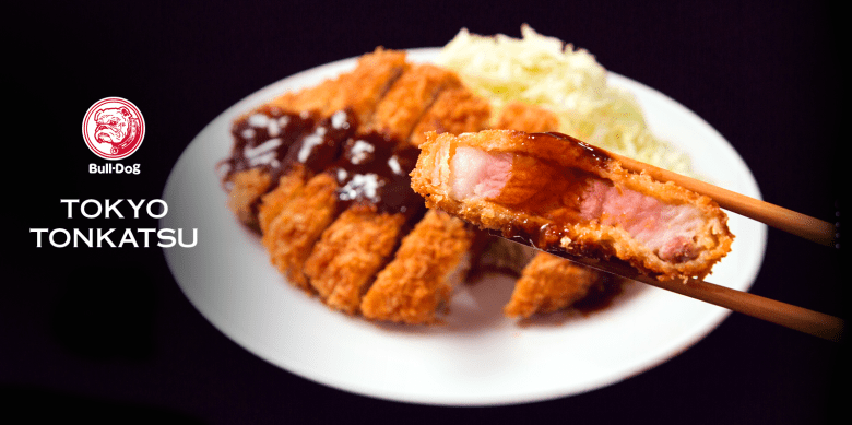 "Photo Description: yum, a black background, with a white plate with crispy juicy tonkatsu and a side of shredded pork. Atop the tonkatsu is bulldog sauce and the text ""bull-dog and tokyo tonkatsu."""