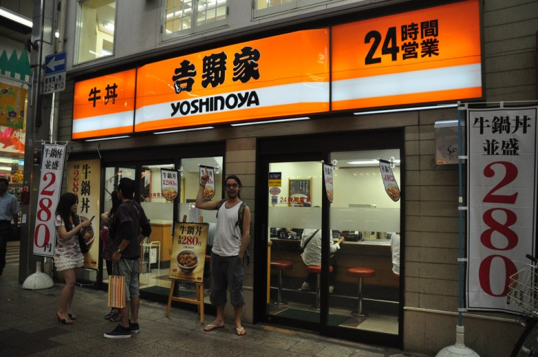 Photo Description: a Yoshinoya exterior in Japan. The first story location is on the corner of a multi-story building. Out front, there are a couple outdoor banners outing their pricing which is touting 280Y. The above Yoshinoya signage states that they are a 24 hr business.