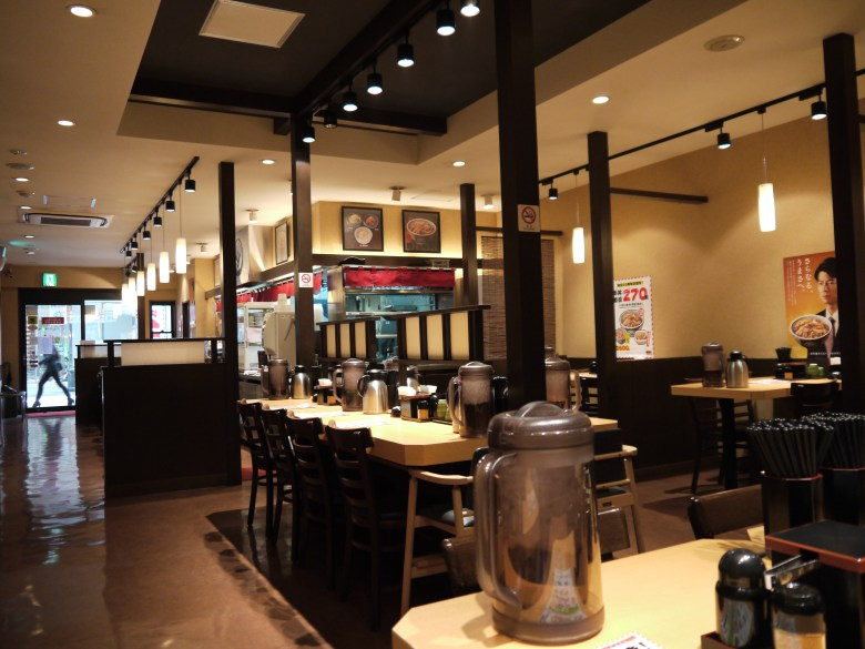 Photo Description: an interior shot of Yoshinoya Kumamoto, Japan. The interior is a clean and contemporary, light colored walls with dark furniture. There are a number of bar height tables with self serve condiments and water pitchers.