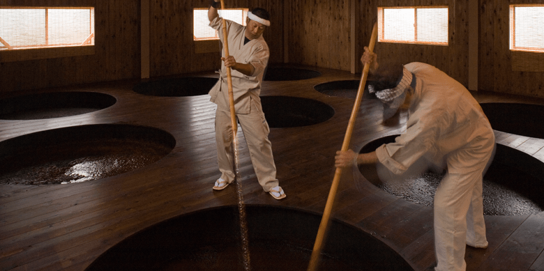 Photo Description: shoyu or soy sauce is being brewed by two individuals dressed in white. They are using long paddles or most likely oar type tools to mix the large vats of shoyu in the all wood building with shoji screen windows.