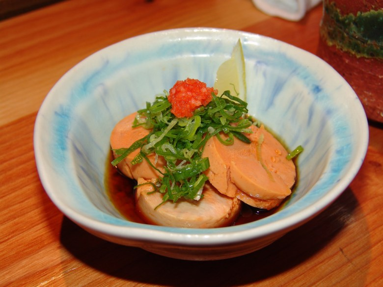 Photo Description: ankimo is steamed monkfish served in a small bowl with ponzu, sliced green onion, momiji oroshi, and a slice of lemon.