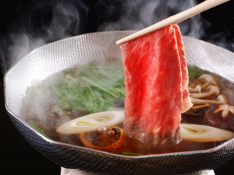 Photo Description: shabu shabu meat is being dipped into the hot water with the veggies, leeks, and mushrooms in it.