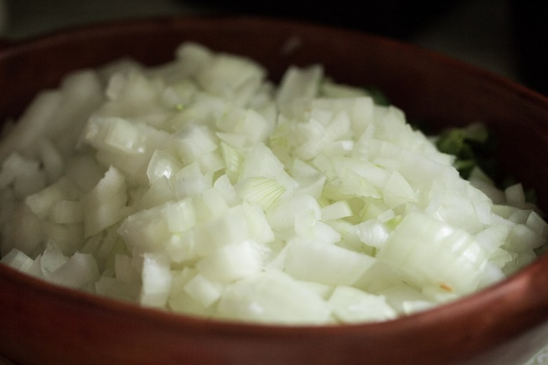 Photo Description: in a brownish round plate, a pile of diced white onions.