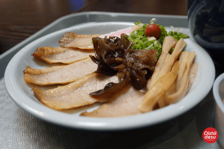 Photo Description: the very iconic side plate of ramen toppings from Santouka ramen. The plate consists of tontoro or pork cheek. The other ingredients are kikurage ramen, negi, menma, naruto, and umeboshi (plum)