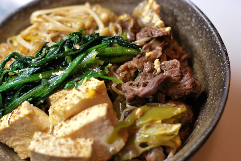 Photo Description: a dark colored Earthen looking bowl with sukiyaki indredients from spinach, tofu, beef, enoki to shirataki or konnyaku noodles underneath.