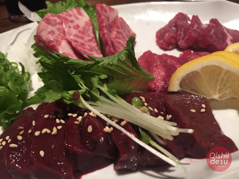 Photo Description: raw beef and raw liver. Thinly sliced lemon, green onion, and oba shiso. Sprinkled on top of the raw liver is sesame seeds.