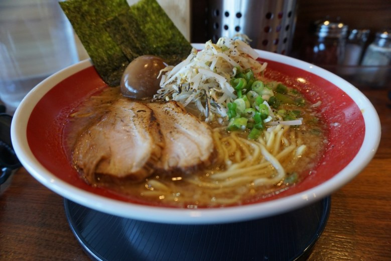 Photo Description: a decent spot in Los Angeles is the Japanese owned and operated Kotoya ramen. The ramen bowl is red with a white trim, with two thick slabs of chashu, moyashi, negi, nori, and ajitama.