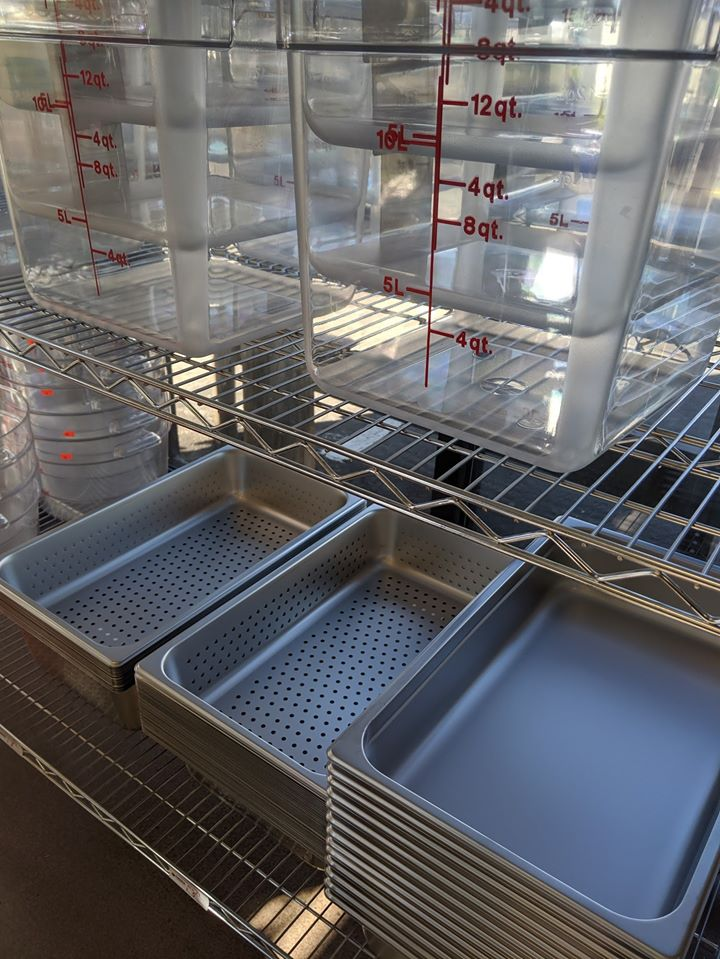 Photo Description: a rack full of commercial kitchen pans to containers from Cambro. If you are wondering how to start a restaurant, you will want to research all the equipment you will need before you purchase it all.