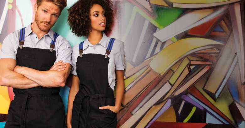 Photo Description: two models stand in front of a colorful abstract mural. Both models, one white dude, and a black chick are wearing aprons that are black with blue suspenders.