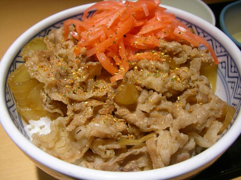 Photo Description: I must be hungry because this looks so good. It is a bowl of gyuondon in a thick walled bowl. Think strips of beef that is a light brown in color topped off with togarashi shichimi and beni shoga (pickled ginger).