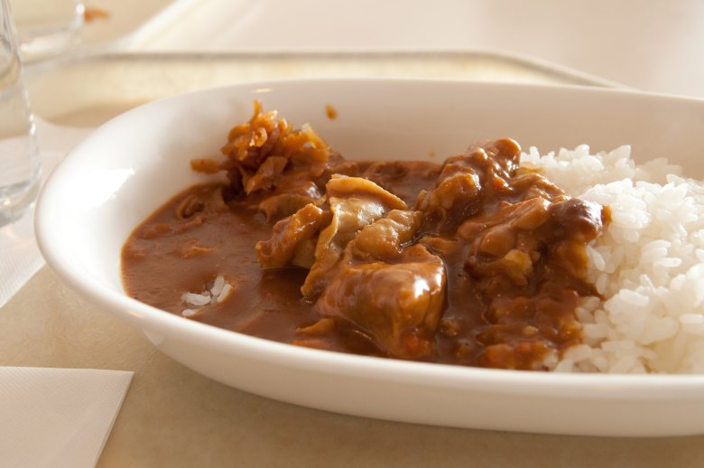 Photo Description: in a white oblong bowl is a mound of rice on one side with a small pool of curry on the left hand side. The brown curry has chunks of meat mixed in.
