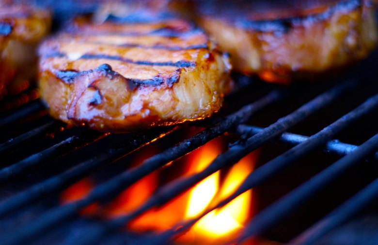 Photo Description: Yum, a picture of several succulent looking pork chops on a grill with the flames below. There is some bokeh in the shot that blurs out the backround.