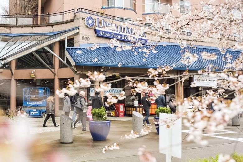 Photo Description: what a shot of Uwajimaya's exterior which looks to be part of an apartment complex because it looks like there's several units above it, but below there are a number of people walking by. In the foreground looks to be cherry blossom trees.