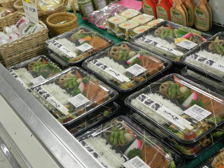 Photo Description: a large open refrigerated items area has a number of Japanese obento's linked up. The black rectangular plastic trays with the clear tops, you can clearly see the rice, vegetables (renkon to edamame) and tonkatsu meals.