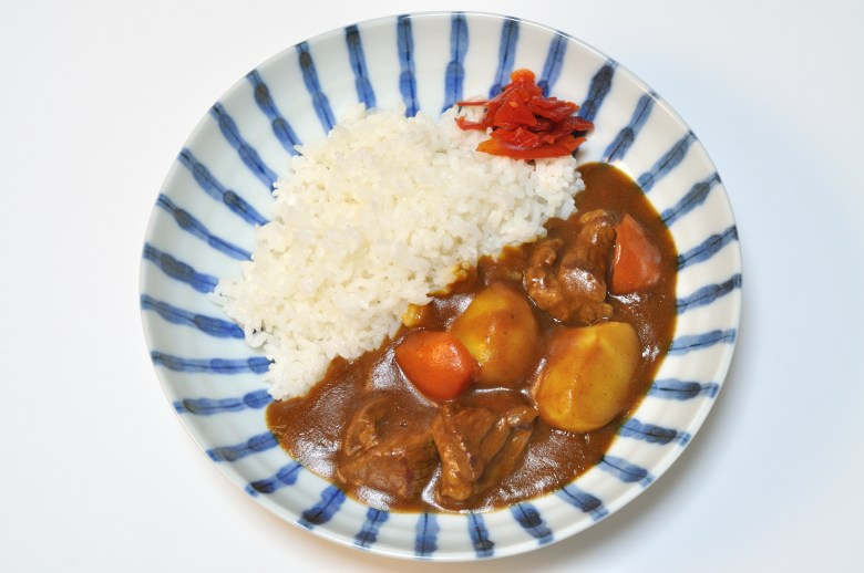 Photo Description: a white background (table) with a plate of curry and rice shot directly above. The rice is on one half, the curry on the other. You can see chunks of potato, beef, and carrot. There's also a small dab of pickled radish that is red in color. The plate has blue stripes radiating out from the center.