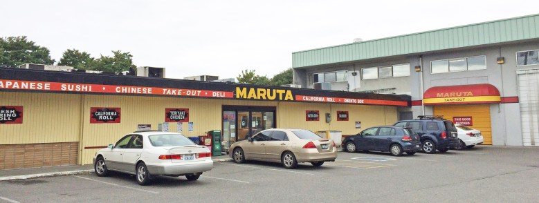 """Photo Description: the Maruta grocery store exterior in Seattle. The one story free standing building looks like it's next to a larger building which may possibly be a warehouse that they own because it says """"Maruta"""" on the awning with the words """"take out"""" on it."""