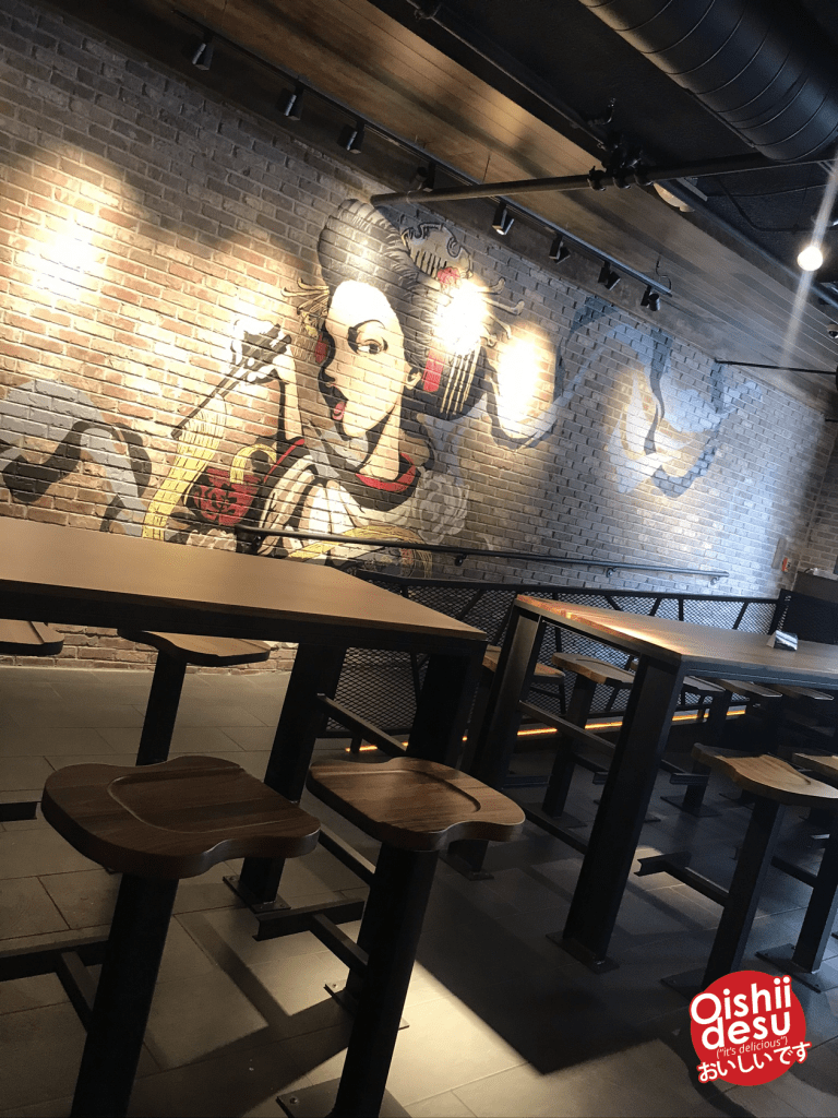 Photo Description: entry way with a ramp with large dark tiles, a brick looking wall with a geisha mural, and two bar height tables.