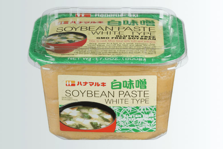 """Photo Description: Packaging of the Hanamaruki shiromiso. The packaging is in a see through plastic container with  the words """"Soybean Paste white type"""". Additional labeling includes """"gluten free"""" and """"GMO free soybean."""""""