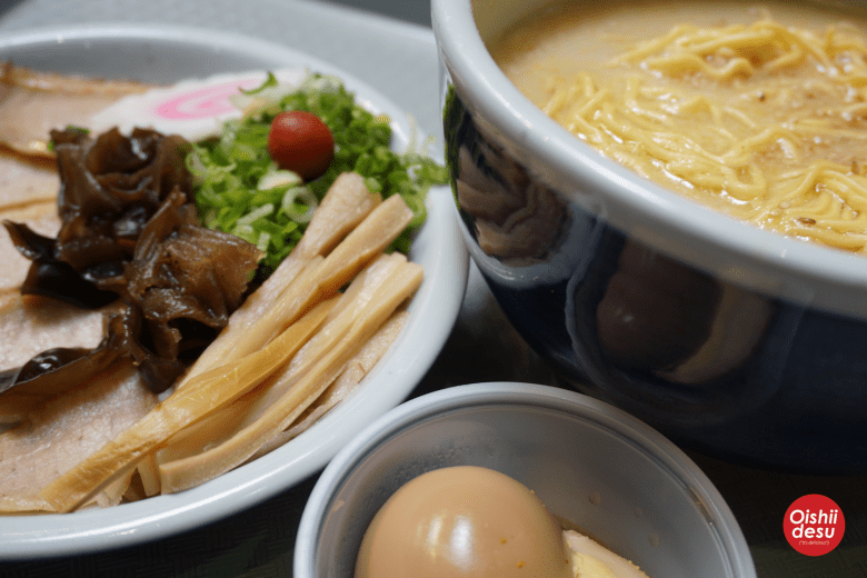 Photo Description: Santouka ramen is authentic Hokkaido style tonkotsu shio ramen. There is ther iconic bowl, fully cooked ajitama, and plate of toppings which include menma, kikurage, negi, narutomaki, chashu, and umeboshi.