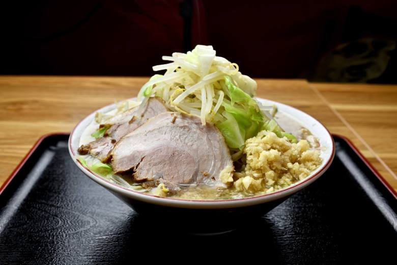 Photo Description: Jiro style ramen has mounds of moyashi, chashu, garlic, and backfat. The bowl is on a black and red tray.