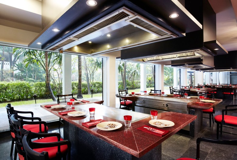 Photo Description: a shot of a dining area of a Benihana in Bangkok, Thailand. The dining area has rows and rows of teppanyaki grills. Each grill has 5 place settings, 3 directly in front and 2 on the side. Directly above each tappanyaki are ducts with spotlighting (5 recessed lights). The seats are red with all black framing. You can see outside due to the large floor to ceiling windows and outside are palm trees.