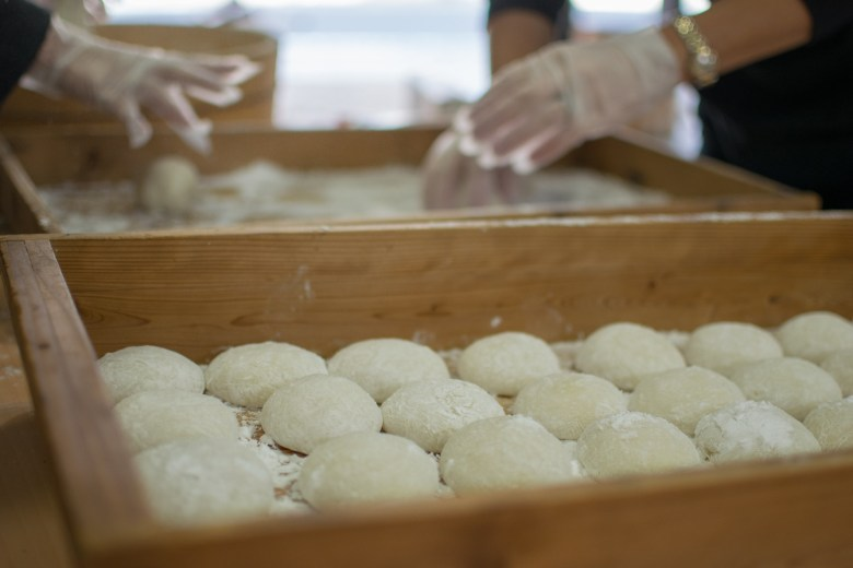 Photo Decription: in Japan, several women are in the final stage of mochi preparation by shaping the the mounds of mashed rice into little cakes/pucks.