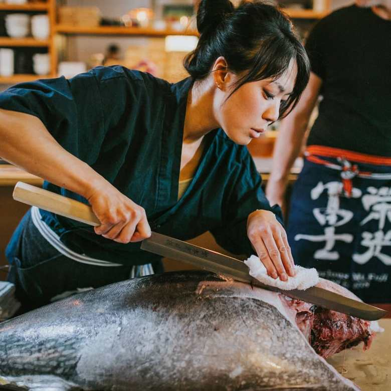 Photo Description: Kate Koo cutting what looks like a tuna with a very large and long blade.