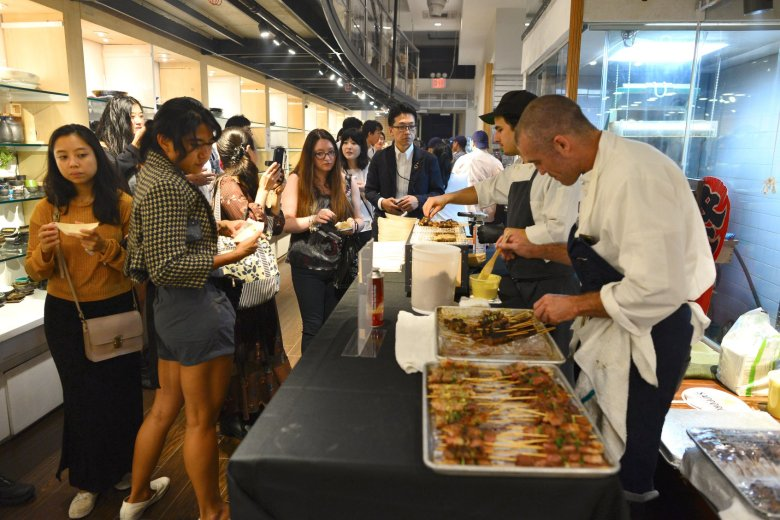 Photo Description: Korin in New York showroom and one of their many events that they host. In this shot several chefs are in their chef whites on the right with apron, an long line of people waiting to be served what looks to be a skewered food.