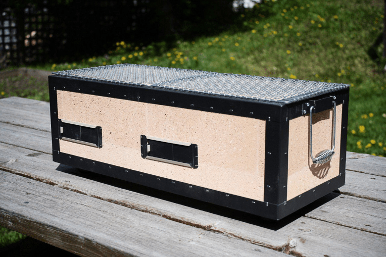 Photo Description: the Kaginushi Kogyo grill is set out on picnic style table. The unit is has an outer black frame around the diatomite bricks.