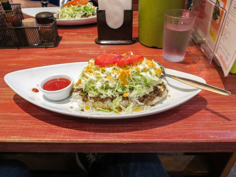 """Photo Description: the other signature dish of Okinawa is taco rice. On an oval style white plate is a mound of what look like white rice, ground beef, lettuce, some sort of yellow looking sauce?, some sliced tomatoes and a side of """"hot sauce"""" which looks more like ketchup."""
