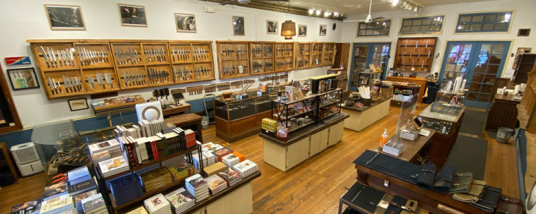 Photo Description: Bernal Cutlery's showroom in the Mission district of San Francisco. The showroom looks huge with several showcases on the wall with what looks like a couple hundred knives displayed. In the center area are a number of books.
