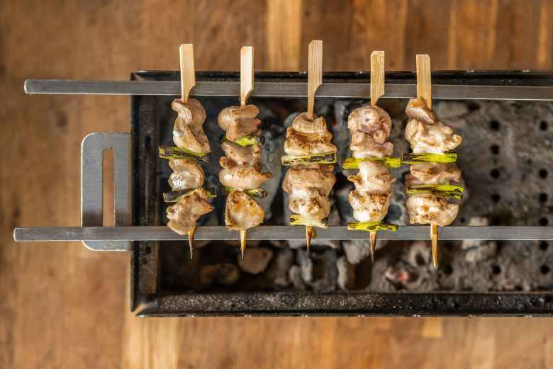Photo Description: 5 negima or chicken skewers with green onions/leeks grilled. This is an above, top down shot that lets you see the burn box with pull out handles.